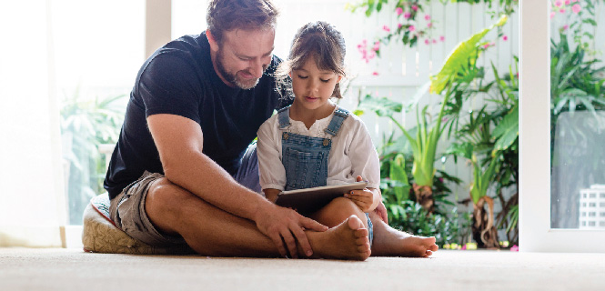 image of father reading a book with his daughter